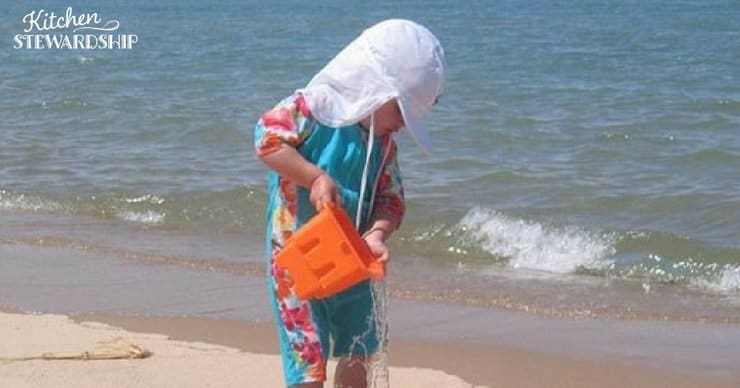Child on a beach in sun-protective clothing