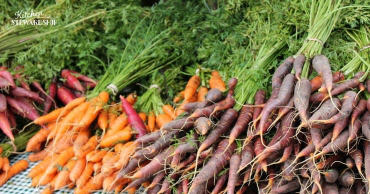 Table full of purple and orange carrots with the stems on.