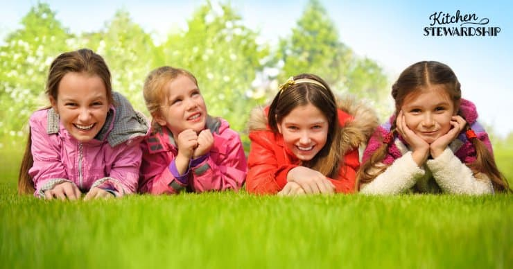 Young girls laying in the lawn.