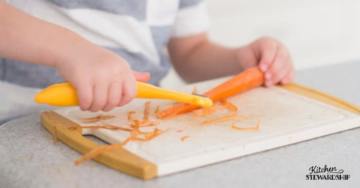 Young boy peeling carrots.