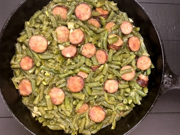 green beans and sausage in a cast iron pan