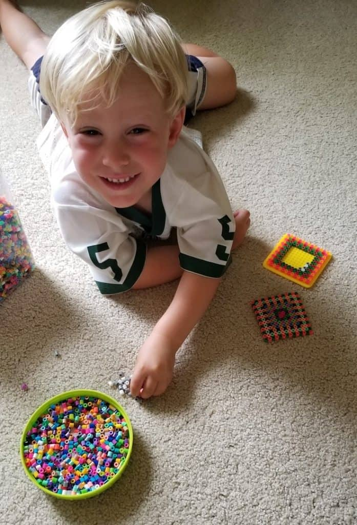 boy playing with beads