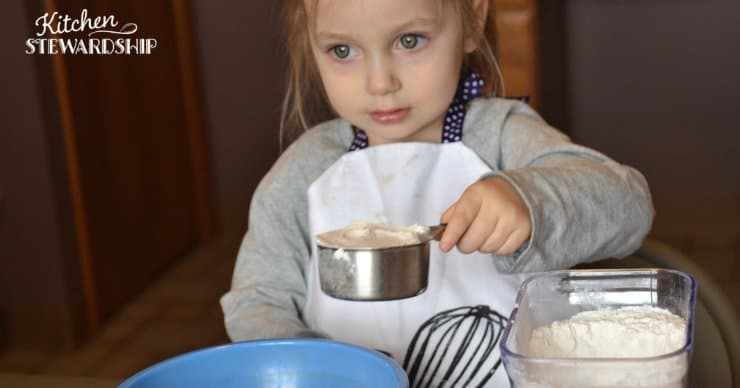 toddler measuring flour