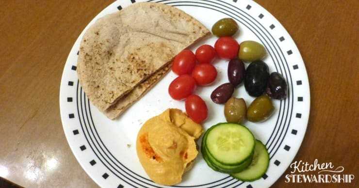 hummus, tomatoes, olives and cucumbers on a plate