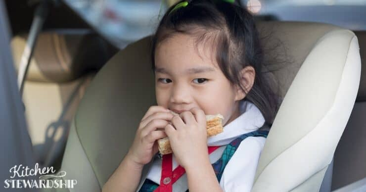 Little girl eating in the car