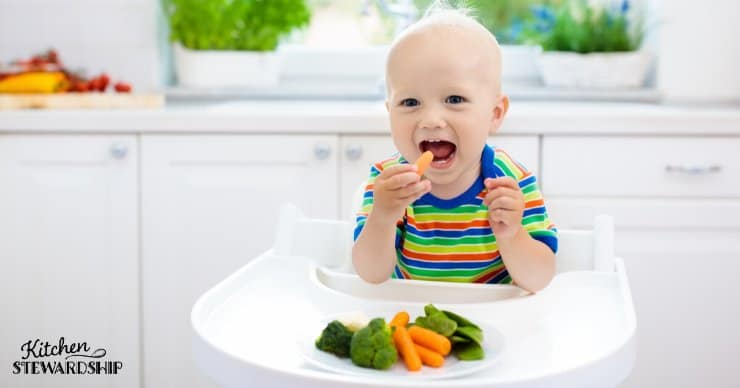 Baby eating carrots and broccoli