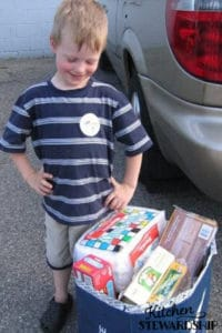 Boy standing by a bag of stuff to donate, non food idea for kid birthday party