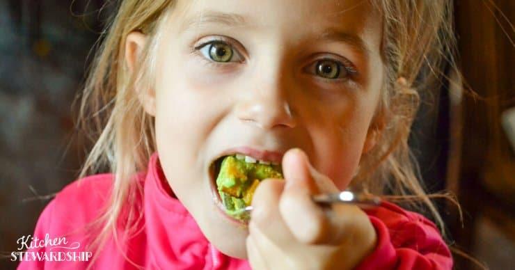 child eating green salad