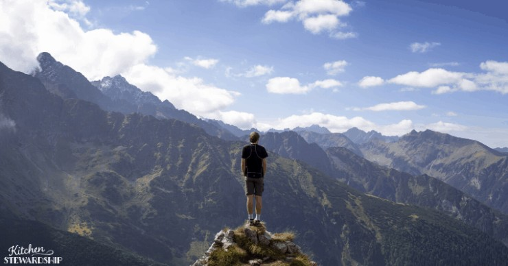 man alone looking at mountains