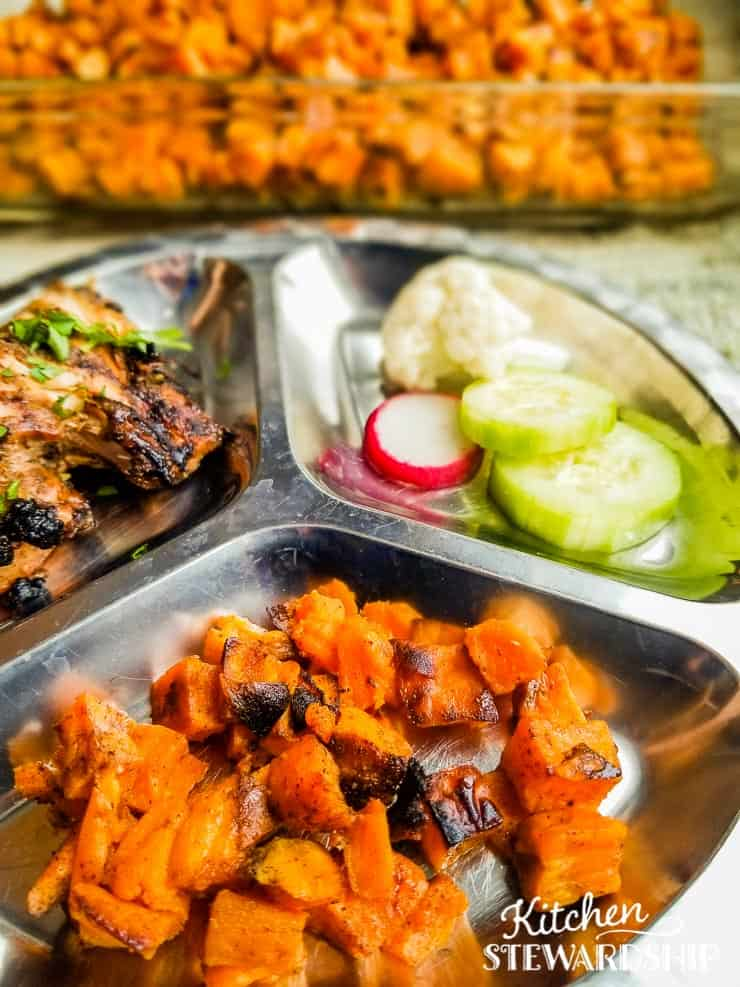 roasted sweet potatoes, chicken, cucumbers on metal plate