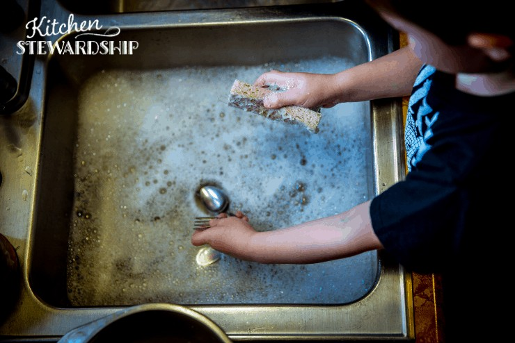 child washing the dishes with non antibacterial soap and sponge