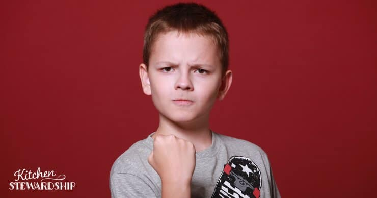 Young boy with an angry or 'hangry' face making a fist