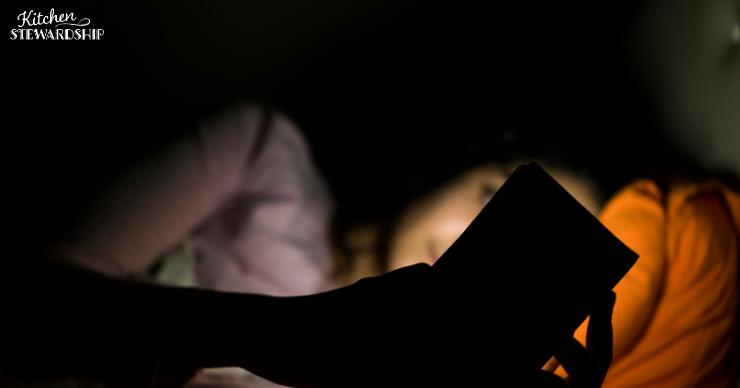 Woman with insomnia using her cell phone while lying awake at night
