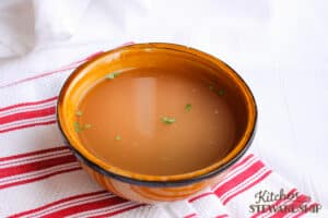 bowl of homemade chicken stock on a red striped hand towel