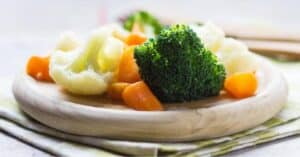 steamed vegetables - broccoli, cauliflower, and carrots - on a circular wooden plate