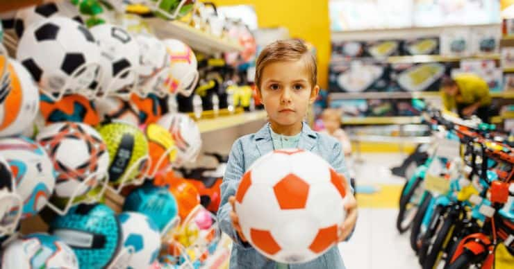 boy holding ball in store