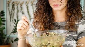 woman holding a bowl of roasted veggie salad