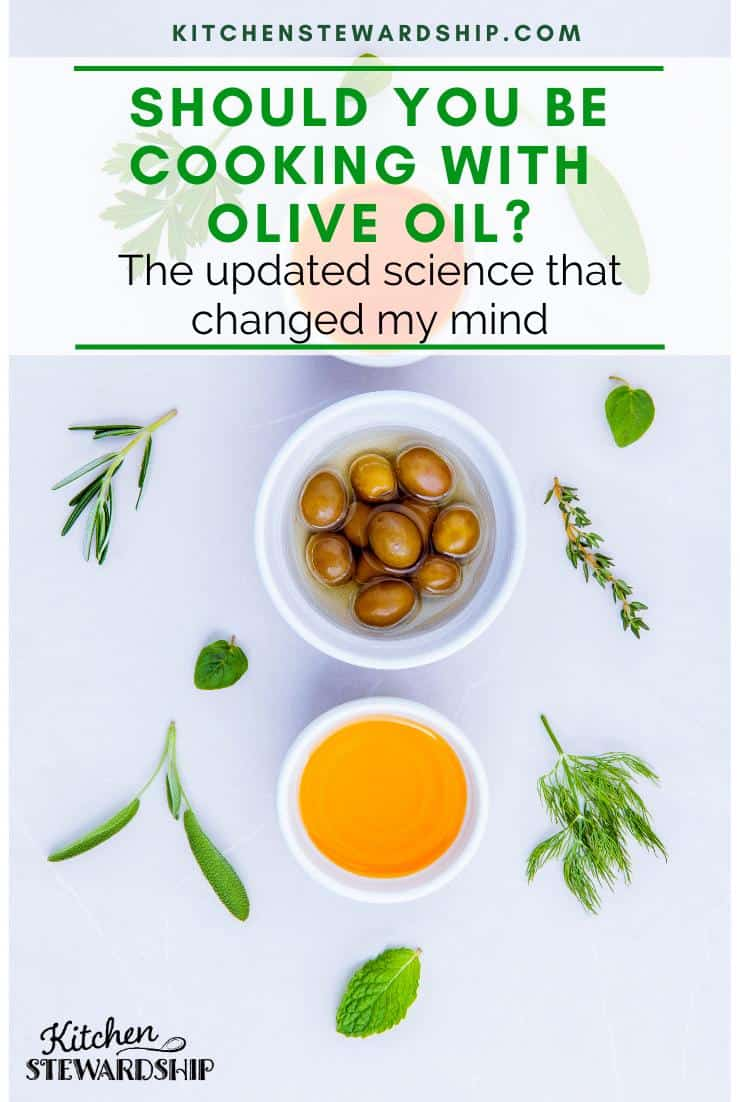 Bowl of olives and 2 bowls of olive oil on a white table with herbs. Should you be cooking with olive oil? The updated science that changed my mind.