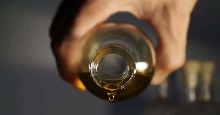 Hand holding a bottle of olive oil ready to pour