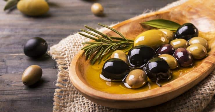 Olives, rosemary, and olive oil in a wooden spoon