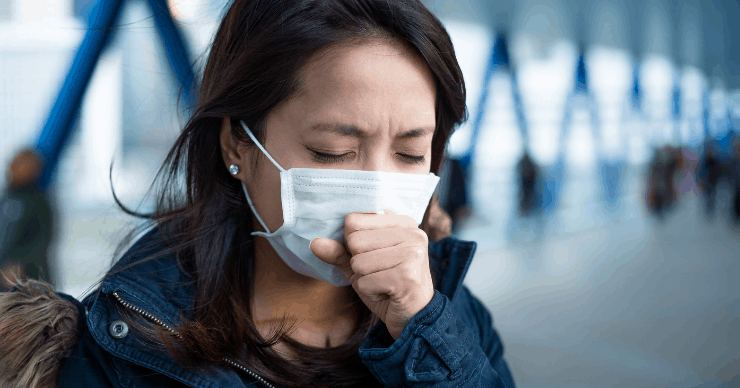 woman coughing into a mask