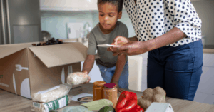 Kid unpacking a healthy meal subscription kit