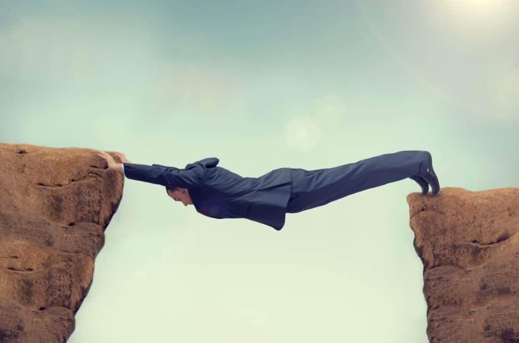 guy hanging between 2 cliffs